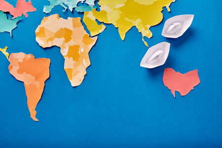 Top view of the white paper boats and international map while cut out of the colored paper on the blue background. Stock Photo