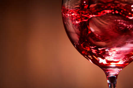Close-up of brightly red wine poured in the wineglass and abstract splashing against brown background. Macro and horizontal photo. Luxury lifestyle. Still-life and background. Sommelier and degustation. Stock Photo