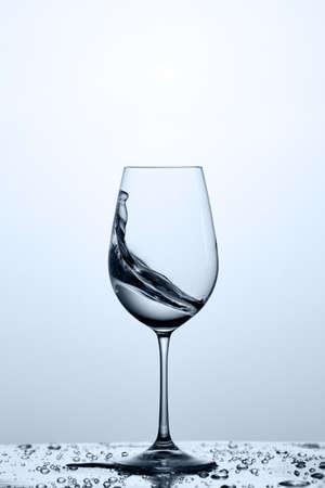 Verre à vin avec éclaboussure d'eau transparente sur le verre avec des gouttelettes sur fond clair.