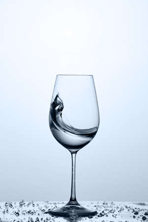 Splashing transparent water wave in the wine glass while standing on the glass against light background.