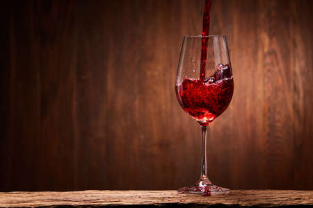 Tasty red wine poured in the elegant glass standing on the wooden stand against wooden wall background. Brightly wine and fragile goblet. Natural material and drink. Concept of the luxury lifestyle. Horizontal photo. Sommelier and tasting. Stock Photo