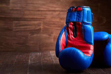 Close-up of the pair of red and blue boxing gloves on the wooden plank.