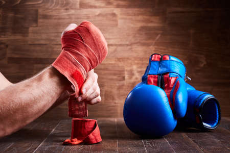 Close-up of the hands of a young boxer who winds boxing bandages and gloves. Horizontal photo of red bandage, blue and red boxing gloves against wooden wall background. Boxing training and exercise. Concept of the sportive lifestyle.