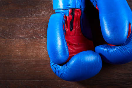 wood texture: Close-up of a pair of boxing blue and red gloves hanging on the wooden wall. Horizontal photo and brown wooden background. Boxing backgrounds and still-life. Training and sportive exercise. Concept of the active lifestyle.