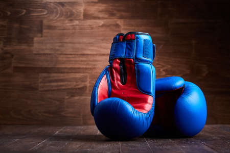 Boxing background with two gloves on the brown plank background. Horizontal photo of the blue and red boxing gloves against wooden wall. Boxing training and exercise. Concept of the sportive lifestyle. Stok Fotoğraf - 78787764
