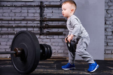 Little sporty child with barbbell against brick wall at the cross fit gym.
