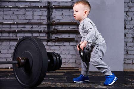 Kleines sportliches Kind mit Barbell gegen Mauer am Kreuz fit Fitness-Studio. Standard-Bild - 79136243