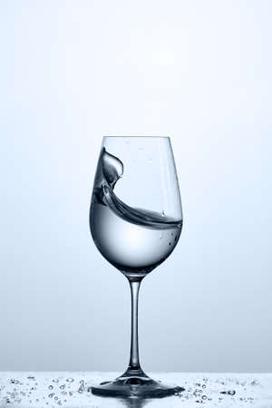Wave of the drinking water in the wineglass while standing on the glass with water bubbles against light background. Stock Photo