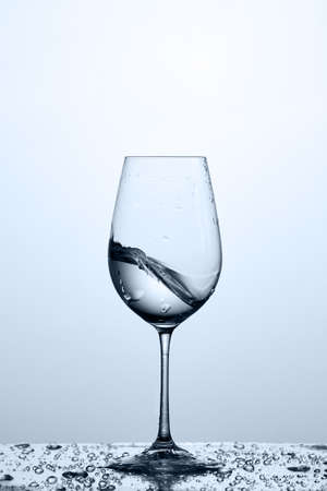 Cleaner and freshness water wave in the wineglass while standing on the glass against light background.