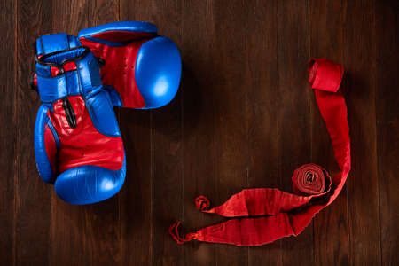 Sport background with blue and red gloves and red bandage on wooden background.