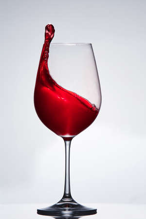Elegant pure wineglass with wave of brightly red wine standing against light background with reflection in down.