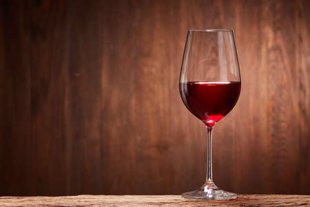 Red wine in the pure elegant wineglass standing on a wooden stand against wooden background. Stock Photo