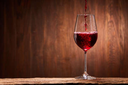 Tasty red wine poured in the elegant glass standing on the wooden stand against wooden wall background.