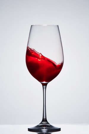 Moving red wine in the elegant wineglass standing against light background with reflection. Stock Photo