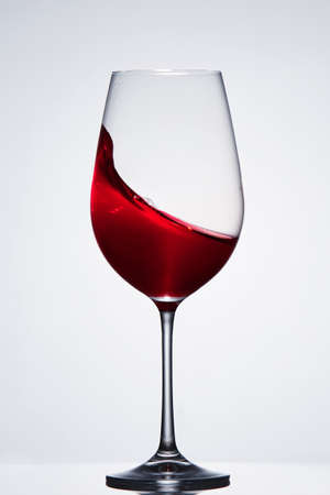 Splashing red wine with wave in the elegant wineglass standing against light background with reflection. Stock Photo