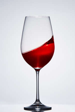 Wave of the romantic drink red wine on the pure wineglass standing against light background with reflection.