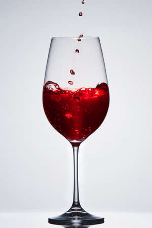 Brightly red wine poured in the fragile pure wineglass standing against light background with reflection in down. Stock Photo