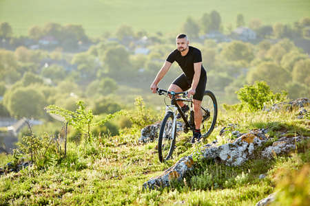 Extreme mountain cyclist riding bike on rocky trail in the countryside. Stock Photo