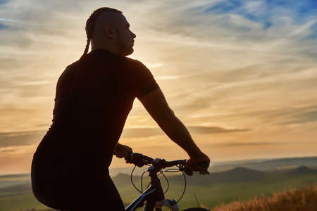 sil: Close-up of silhouette of cyclist standing with bike against beautiful sunset. Sportsman in the sportwear. Extreme travelling in the countryside. Beautiful landscape. Concept of the healthy and active lifestyle.