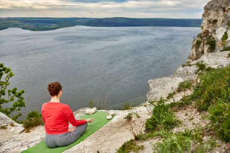 Young woman is doing yoga exercises on the rock above beautiful river. Sportive woman in the sportwear on the green yoga mat. Beautiful landscape and sky with clouds like a background. Concept of the healthy lifestyle.