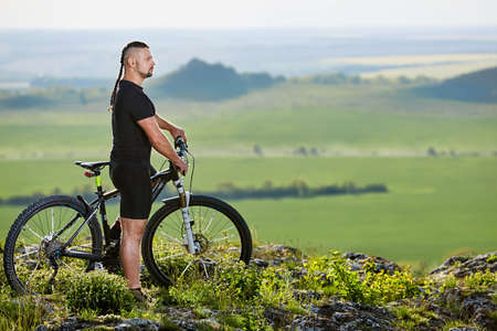 Cyclist standing with mountain bike on background of beautiful landscape.