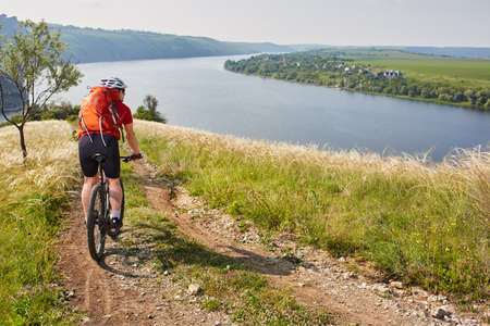Rear view of the young attractive cyclist riding mountain bike in the summer meadow. Sportsman in the sportwear, with helmet and sunglasses. Extreme travel in the countryside. Concept of the healthy lifestyle. Stock Photo