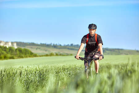 Attractive cyclist rides on the road in a field on a bright sunny day against blue sky. Stock Photo