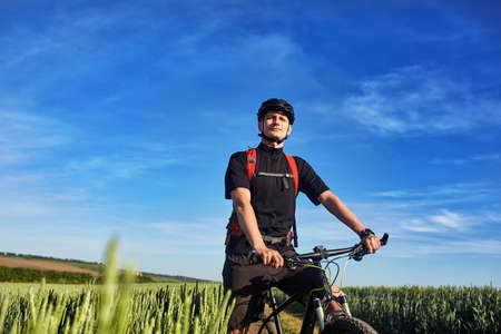 Young cyclist standing with mountain bike on background of beautiful landscape. Stock Photo