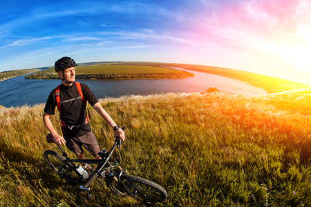 Attractive cyclist standing on the hill with mountain bicyclist against beautiful river. Stock Photo