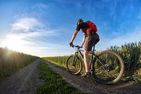Cyclist in the helmet riding mountain bicyclist on outdoor trail against sunrise. Stock Photo