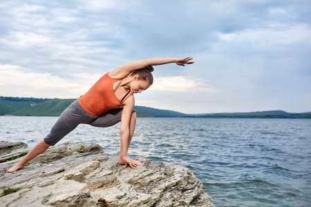 Young woman standing in yoga pose on the big stone near beautiful river. Stock Photo