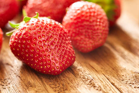 estate: Close-up of the fresh red strawberries on the brown wooden table.