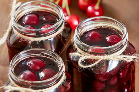 marmelade: Cherry jam on wooden background in the jars