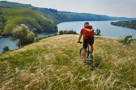 Attractive cyclist riding mountainbike on the meadow above river in summer season in the countryside. Stock Photo