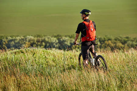 stands: Rear view of the sportsman with his mountain bike stands on the meadow and looking away in the countryside. Stock Photo