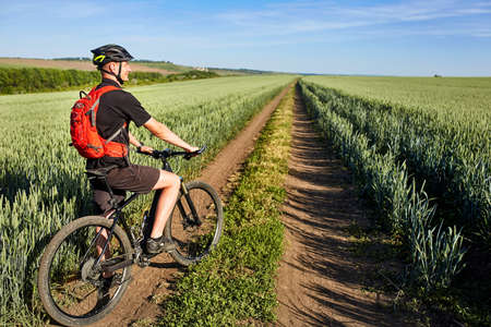 Attractive one cyclist on mountainbike on path near green fields in the countryside in the summer season. Stock Photo