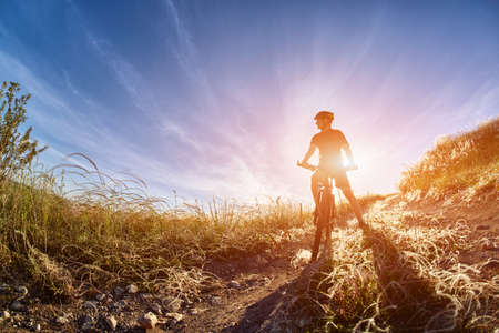 Young cyclist with mountain bicyclist on the path of the field in the countryside against sunrise. Stock Photo