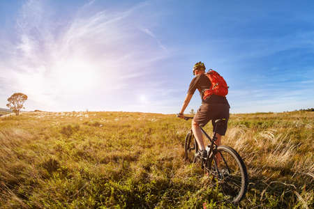 Attractive one cyclist on mountainbike on path near green fields in the countryside in the summer season. Фото со стока