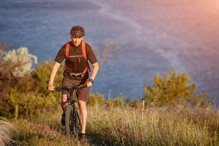 Young man riding mountain bike on the green meadow above the blue river in the countryside. Stock Photo