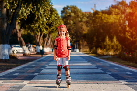 Pretty little girl in red t-shirt learning to roller skate outdoors on beautiful summer day