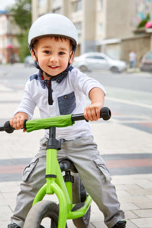 Little boy kid in helmet ride a bike in city park. Cheerful child outdoor.