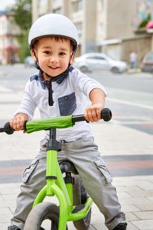 road bike: Little boy kid in helmet ride a bike in city park. Cheerful child outdoor.