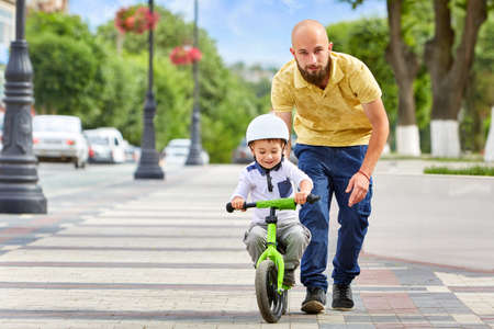 First lessons bicycle riding. Father teach his son to ride a bike.