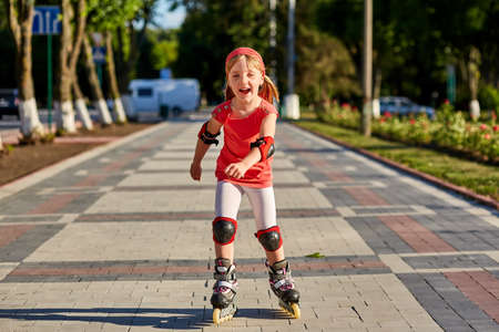 blading: Girl riding on roller skates in skatepark summer outdoor. Child in a red suit for the rollers Stock Photo
