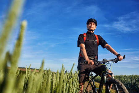 velo: Attractive one cyclist on mountainbike on path near green fields in the countryside in the summer season. Stock Photo