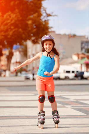 Cute little girl learning to roller skate in city skate park on beautiful summer day.