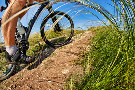 cyclist man feet riding mountain bike on outdoor trail in sunny meadow