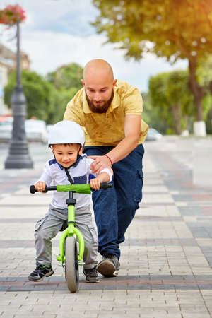 road bike: Father help his son ride a bicycle Stock Photo
