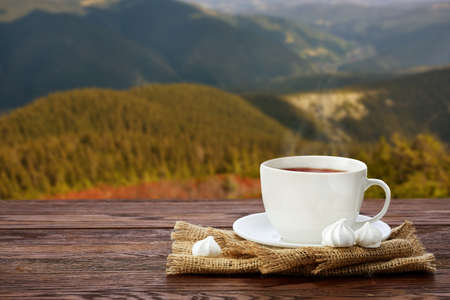 Tea cup with and tea leaf sacking on the wooden table and the mountain background Stock Photo