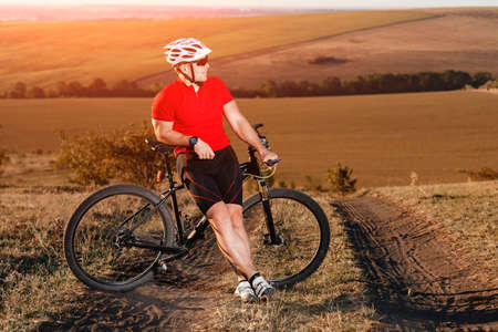 young bright man on mountain bike riding in autumn landscape